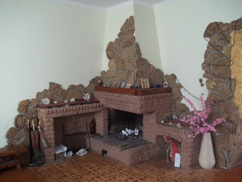 Угловой камин на снимке декорирован двумя видами керамогранита