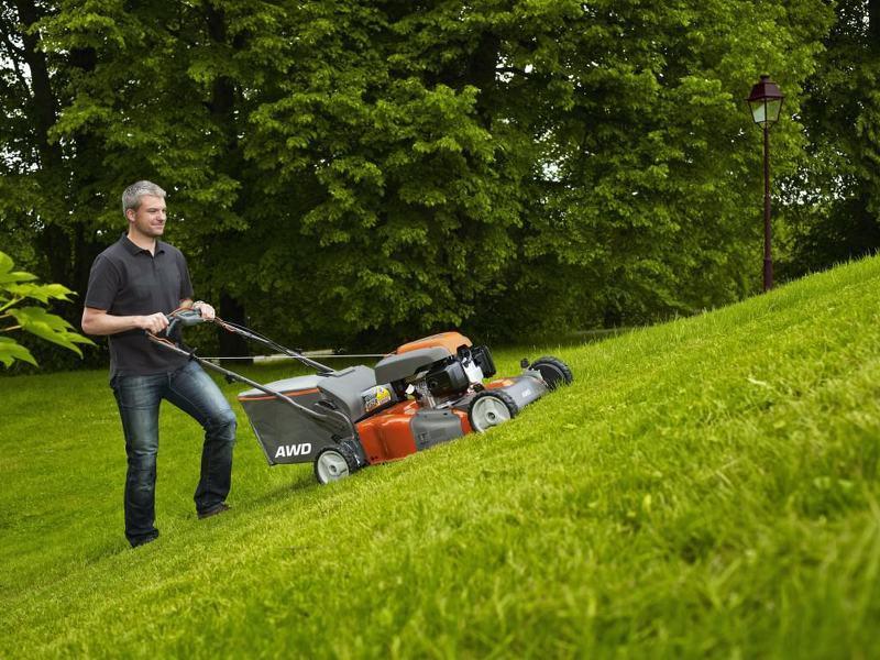 Стрижка газона на холме весной